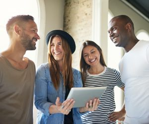 Group of four young stylish friends laughing and watching something on tablet in light modern room.