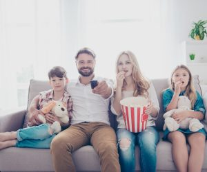 Fun time together. Happy family of four is watching interesting educational documentary, eating popcorn, at home on a couch